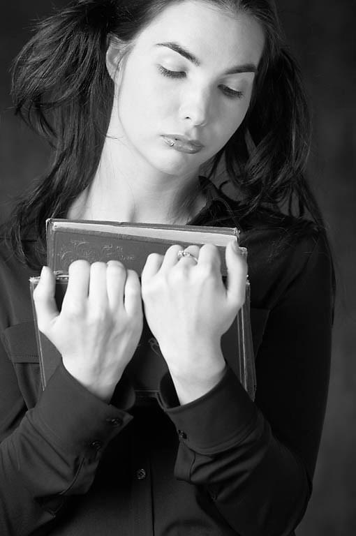 nainen pitelee kirjoja sylissään