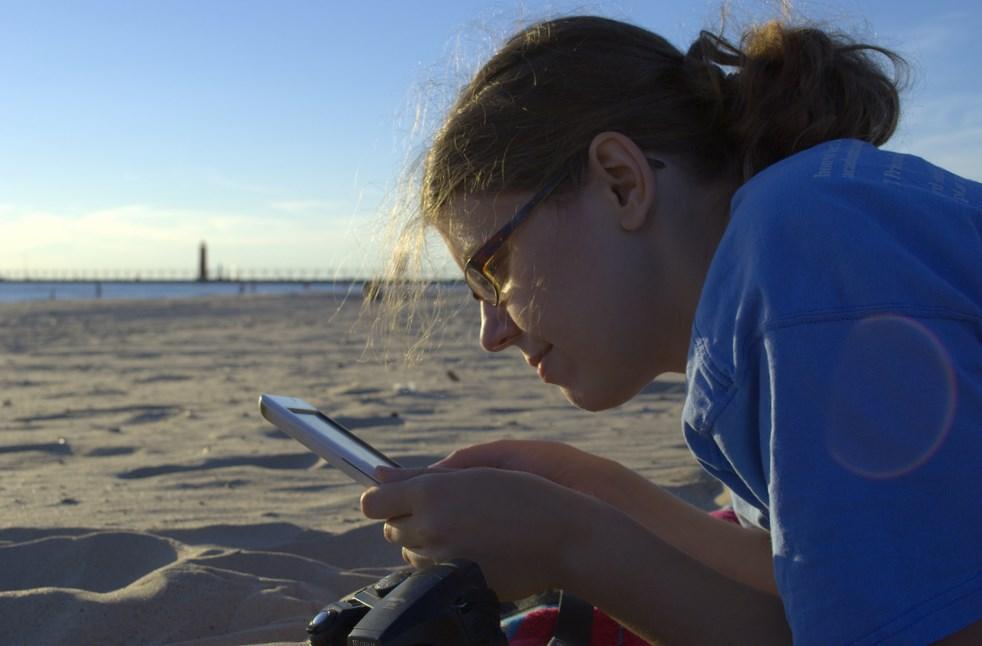 nainen lukee e-kirjaa rannalla lukulaitteesta. Kuva: Michael Mol.