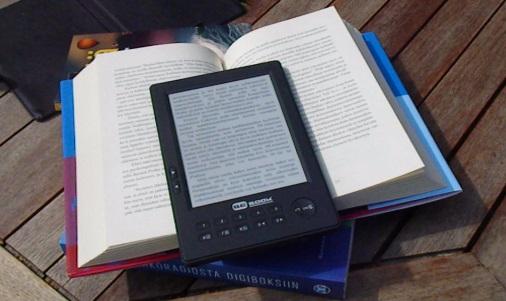 e-kirjojen lukulaite Bebook ja paperikirjoja auringonvalossa