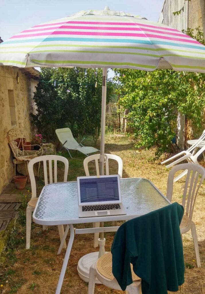 etätyö työpöytä puutarhassa, kannettava tietokone