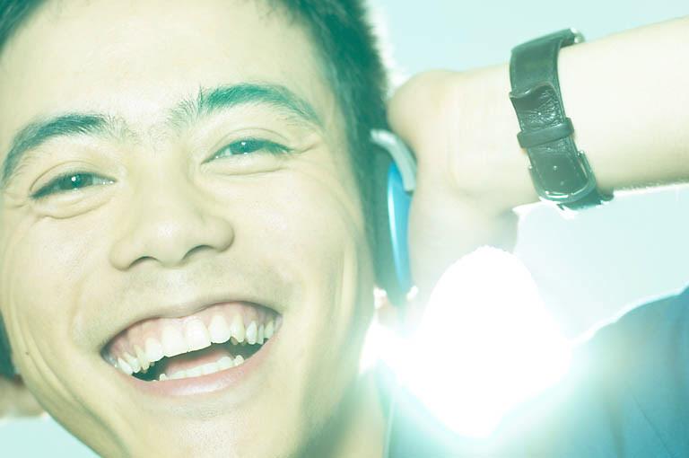 nuori mies kuuntelee kuulokkeilla hymyillen
