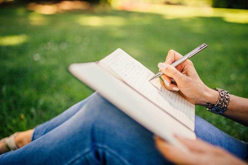nainen ruohikolla kirjoittaa kynällä vihkoon