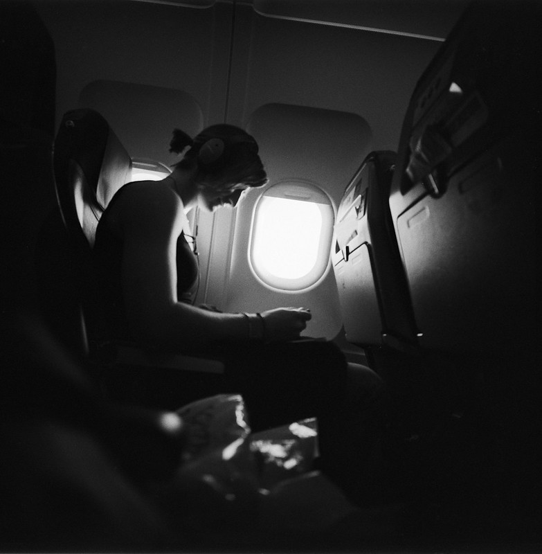 woman reading in airplane by edward conde