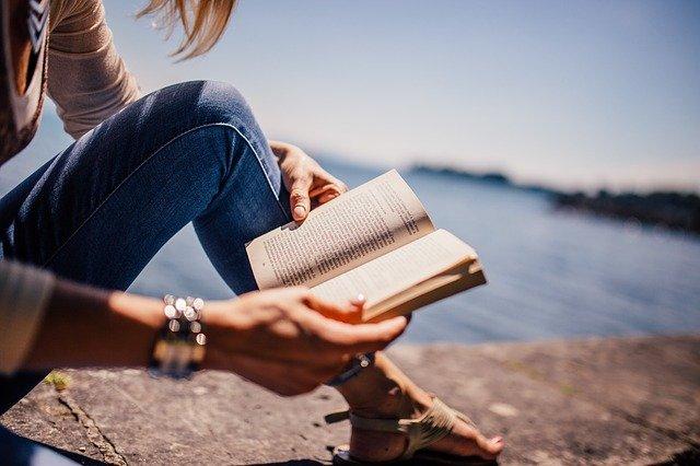 nainen lukee kirjaa rantamuurilla