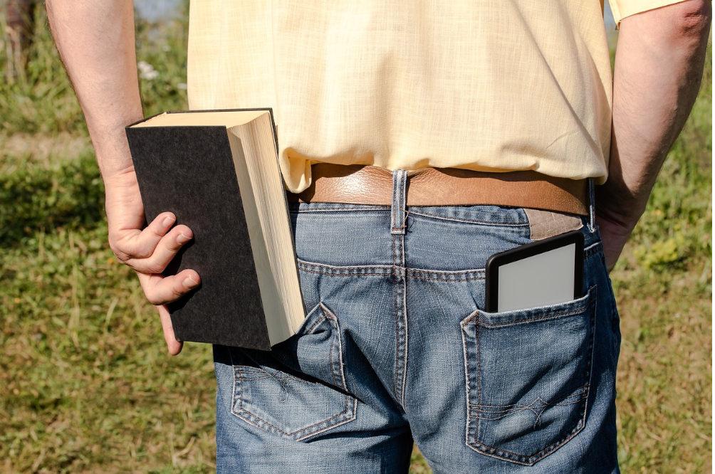 e-kirjojen lukulaite ja painettu kirja housujen taskussa. kuva: Myriam-photos.